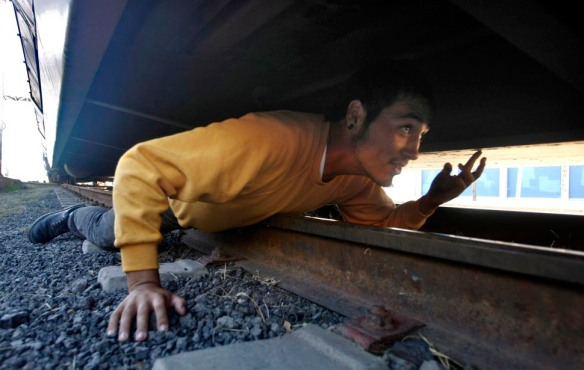 Nogales, Mexico — Lying prostrate across the rails, Luis Luna nervously tries to figure out how to crawl up into the undercarriage of a freight car. He's done it before, but he has only seconds before the U.S.-bound automobile carrier starts moving again.