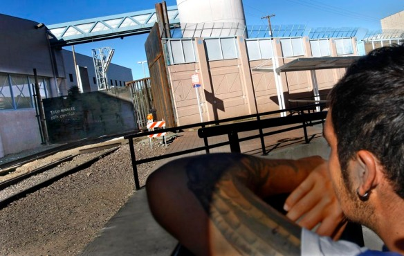 "Nogales, Mexico — Having failed to get on a northbound freight train, Luis Luna looks at the locked steel gate that spans the U.S./Mexico border. ""You get more depressed with the border just a few feet away,"" he said. ""Just more torture."""