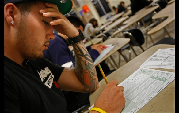 Los Angeles — Luis Luna takes a placement exam in an effort to earn his high school diploma. He was deported before he could graduate from high school.
