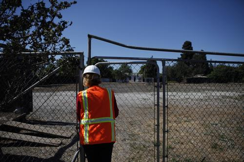 Off-limits for now ( Katie Falkenberg / Los Angeles Times / June 29, 2012 ) Sue Gordon, a vice president of Rainbow Environmental Services, locks the gate to the historical Japanese community of Wintersburg that the company now owns.